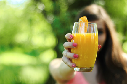Girl saying cheers with orange juice